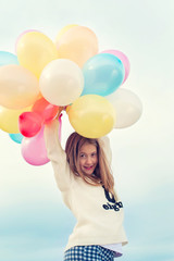 Cheerful young trendy girl with bunch colored balloons