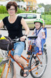 Woman with child rides a bicycle