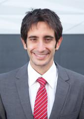 Portrait eines lachenden Geschäftsmanns mit schwarzen Haaren