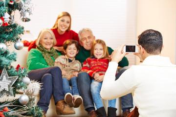 Vater fotografiert Familie an Weihnachten
