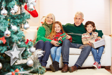 Großeltern mit Enkeln neben Weihnachtsbaum