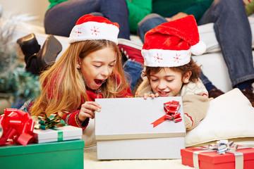 Kinder öffnen Geschenke an Weihnachten