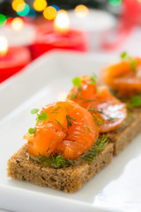 Delicious appetizer canapes of black bread with smoked salmon