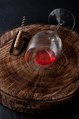 Glass red wine and  corkscrew on dark background