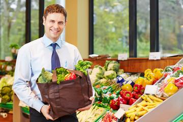Geschäftsmann mit Gemüse im Bioladen