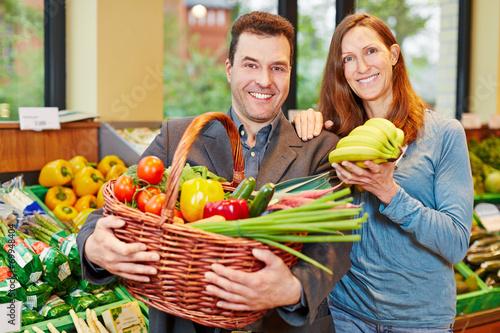 canvas print picture Paar im Bioladen kauft Obst und Gemüse