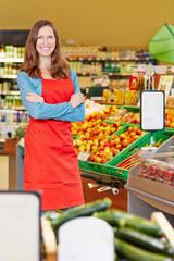 Lächelnde Verkäuferin steht im Supermarkt