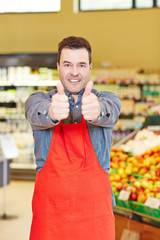 Verkäufer hält Daumen hoch im Supermarkt