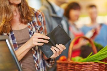 Hand sucht Geld in Brieftasche