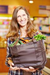 Frau im Supermarkt hält volle Einkaufstasche