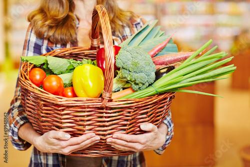 Hände tragen Einkaufskorb voller Gemüse - 69948862