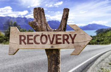 Recovery wooden sign with a road background