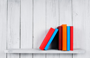 Books on a wooden shelf.