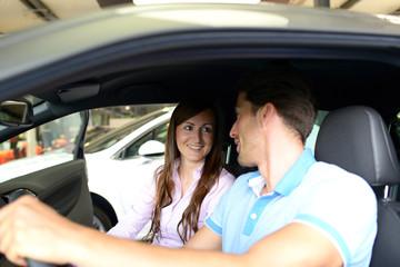 junges Paar testet Neuwagen im Autohaus