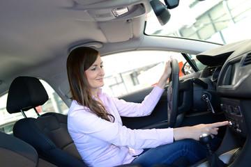 hübsche Frau testet Neuwagen im Autohaus
