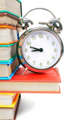 Alarm clock and multi-coloured books.