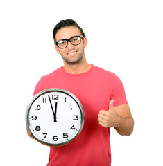 Happy young handsome man holding clock in his hand with thumb up