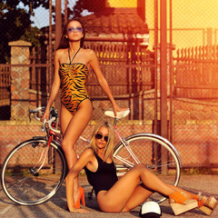 Two sexy model girls posing near a vintage bike. Outdoor fashion