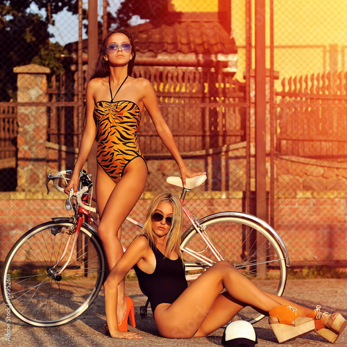 canvas print picture Two sexy model girls posing near a vintage bike. Outdoor fashion