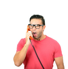 Portrait of young man yelling at phone against white background