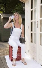 Female painter decorator drinking a mug of tea