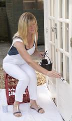 Female painter decorator painting windows