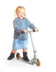Little girl riding her children scooter.
