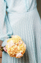 Woman holding bouquet of yellow carnation and pink pastel roses