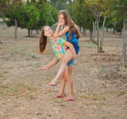 Two best friend girls piggy-backing