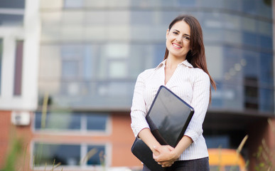 Happy business woman holding laptop and smiling