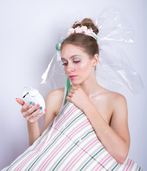 Girl-marshmallow with a pillow and alarm clock in her hands.