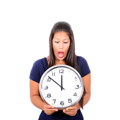 Portrait of a young female in shock holding big clock against wh