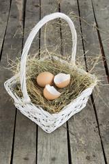Egg and broken eggshell on hay in white basket