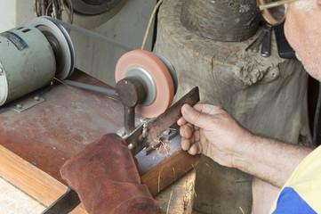 Old man sharpening blade for mower