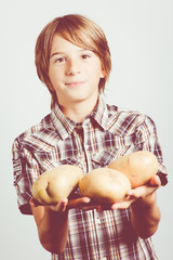child with big potatoes