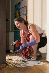 woman uses heat gun to scrap paint on home trim