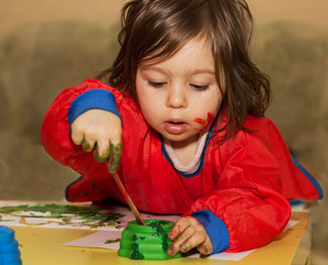 Cute little child drawing and studying at daycare