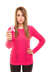 Serious young woman in pink sweater with breast cancer ribbon