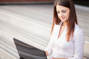 Portrait of a smiling young woman using laptop on outdoors