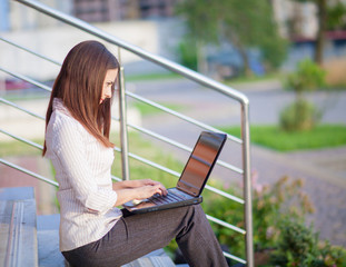 A shot of business woman working on her laptop outdoor