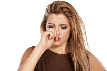 frowning young woman scratching her nose