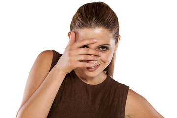 ashamed smiling young woman looking through her ​​fingers
