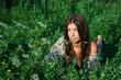 Nice girl among green grass and flowers