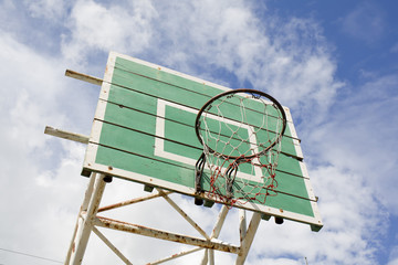 A basketball basket on weathered green wooden facade. Basketball
