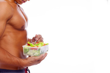 Muscular man holding a bowl of fresh salad on a white background