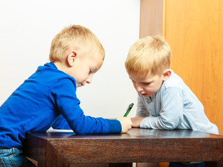 boys children with pen writing doing homework. At home.