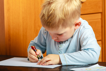 boy child with pen writing doing homework. At home.