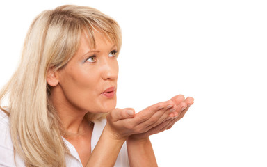 Portrait of mature woman blowing a kiss isolated