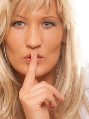 Woman asking for silence finger on lips hush gesture.