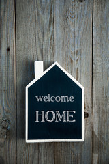 House Shaped Chalkboard sign on rustic wood WELCOME HOME